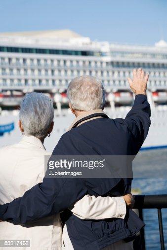 Couple Waving To Cruise Ship Stock Photo