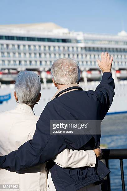 Couple waving to cruise ship