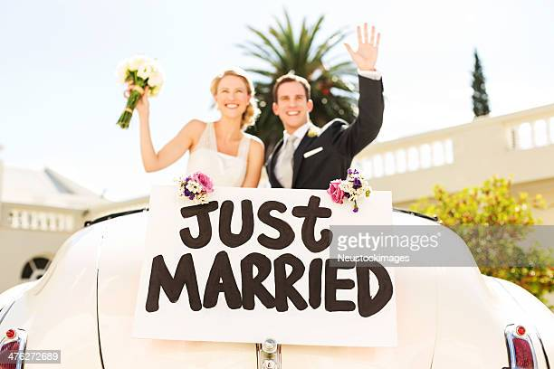 couple waving with just married sign attached car - newlywed stock pictures, royalty-free photos & images