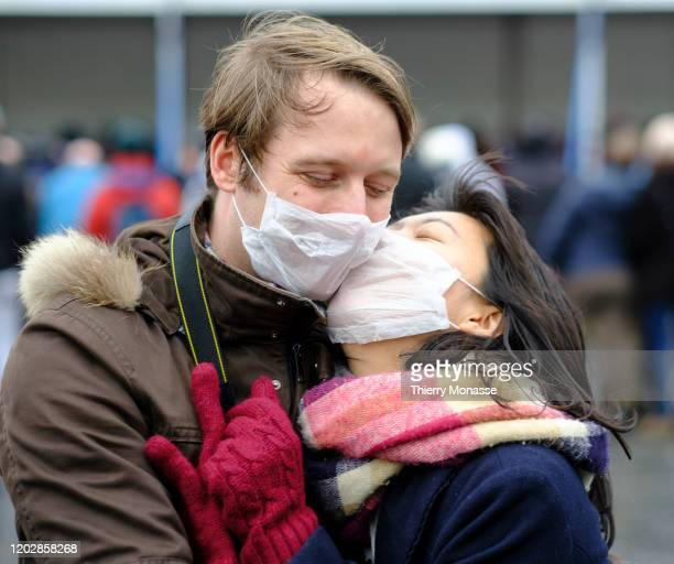 Couple wear anti-coronavirus masks during the 92st edition of the Aalst Carnival parade on February 23, 2020 in the streets of Aalst, Belgium. The...