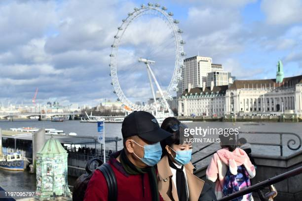 A couple wear face masks as they walk along the Thames embankment in central London on January 28 2020 Around 1500 people who came to Britain from...