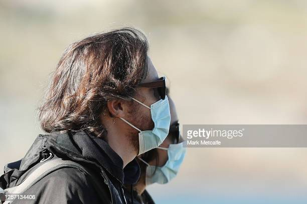 Couple wear face masks while walking at Bondi Beach on July 20, 2020 in Sydney, Australia. People across New South Wales are being encouraged to wear...