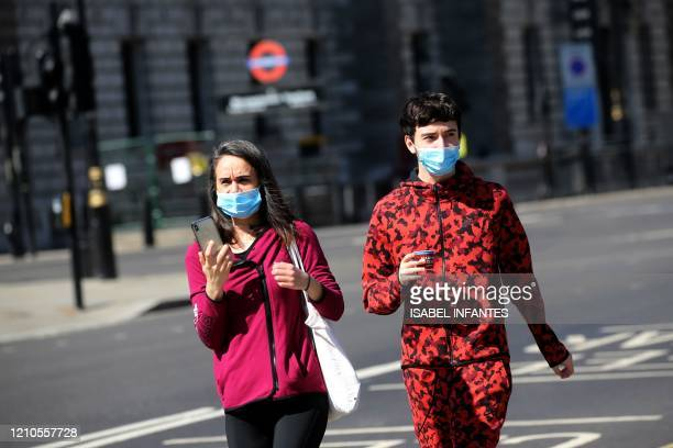A couple wear facemasks as they walk near the Houses of Parliament in Westminster central London on April 21 during the nationwide lockdown to combat...
