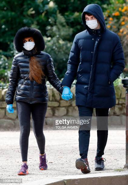 A couple wear gloves and face masks as a precautionary measure against Covid19 as they walk to get their daily exercise allowance in Battersea Park...