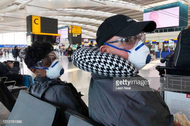 A couple wear protective masks and goggles as they prepare to board a flight to the Bahamas at terminal 5 of Heathrow Airport on March 16 2020 in...
