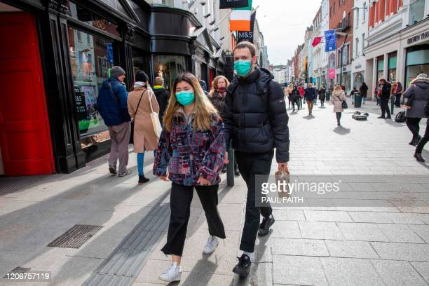 A couple wear surgical masks while shopping in the Grafton shopping area of in Dublin on March 12 2020 Ireland on Thursday announced the closure of...