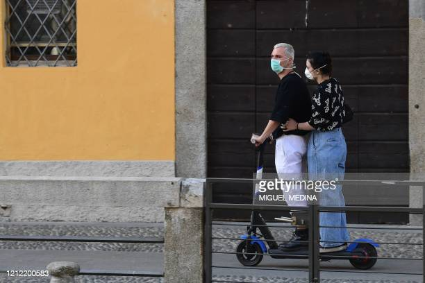 Couple wearing a face mask rides an electric scooter along a Navigli canal in Milan on May 8, 2020 during the country's lockdown aimed at curbing the...