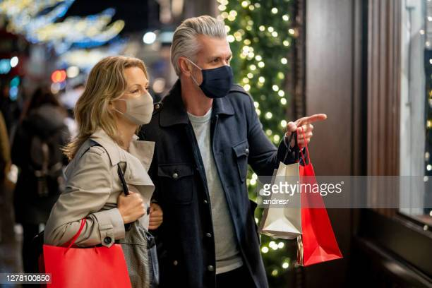 couple wearing a facemask while christmas shopping in london - retail stock pictures, royalty-free photos & images