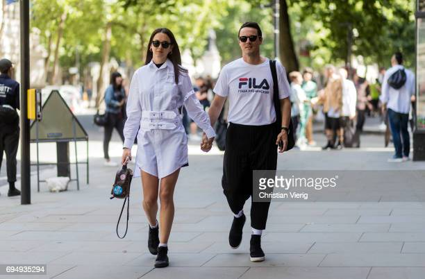 A couple wearing a Fila tshirt Louis Vuitton backpack during the London Fashion Week Men's June 2017 collections on June 11 2017 in London England