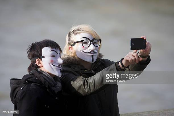 A couple wearing Anonymous masks pose for their own selfie photo Holding up a smartphone to take the picture the person on the right touches the...