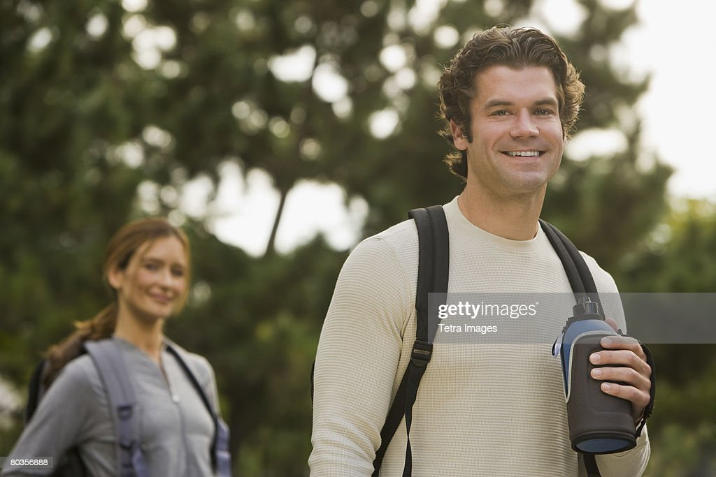 Couple wearing backpacks in woods : Stock Photo