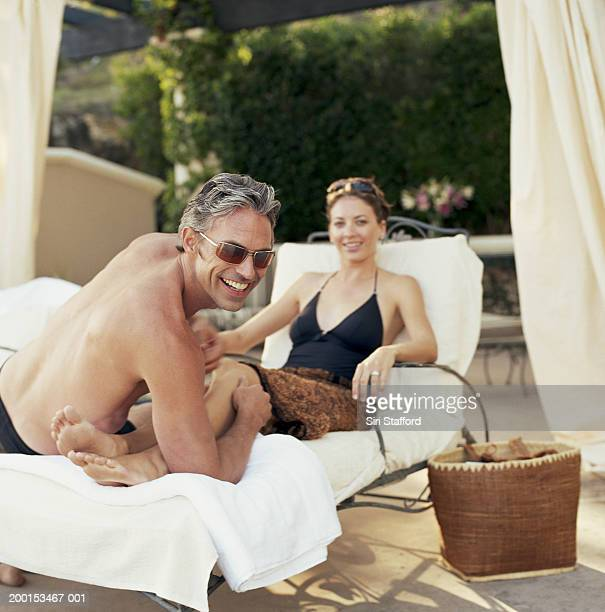 Couple wearing bathing suits, sitting on lounge chair, portrait