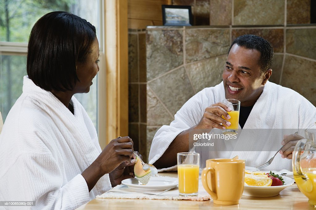 Couple wearing bathrobes, eating breakfast at table : Foto stock