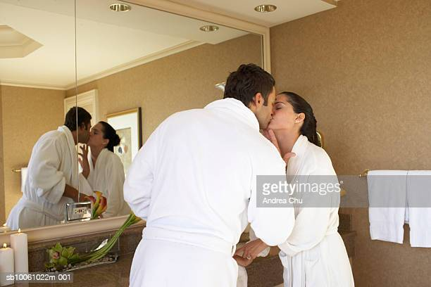 Couple wearing bathrobes kissing in bathroom