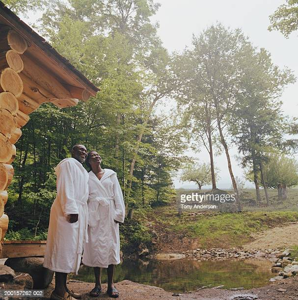 couple wearing bathrobes outside sauna, looking upwards - black woman in sauna stock pictures, royalty-free photos & images