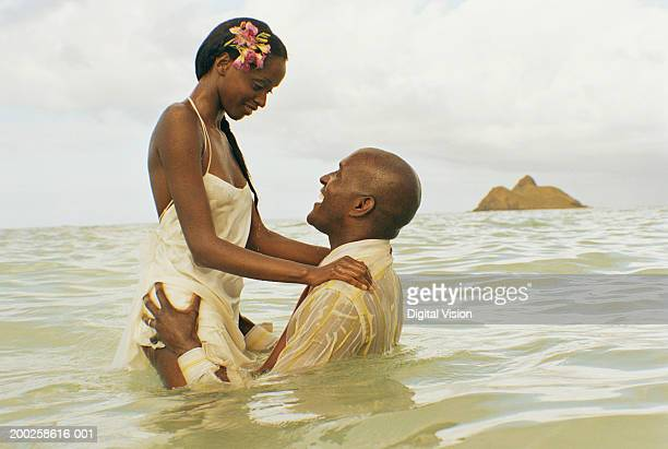 Couple wearing clothes in ocean, man holding up woman