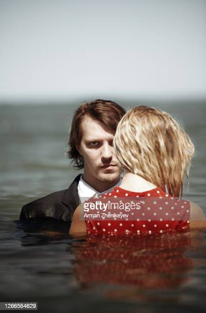 couple wearing dressy attire and standing in the sea - heterosexuelles paar stock-fotos und bilder
