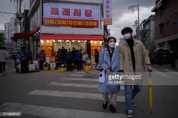 TOPSHOT A couple wearing face masks amid concerns over the COVID19 novel coronavirus walks through a market in Seoul on April 22 2020