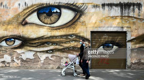 Couple wearing face masks and pushing a pram walks past a mural in the Trastevere district of Rome on April 13, 2020 during the country's lockdown...