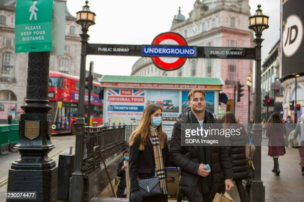 Couple wearing face masks as a precaution against the spread of covid 19 walking out of Piccaadilly underground Station in London.