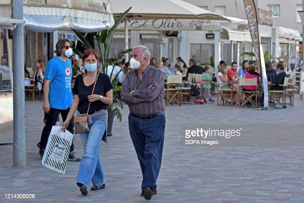 A couple wearing face masks as a precaution walking along Paseo Maritmo street during the end of the confinement of Phase One Calafell is in Phase...