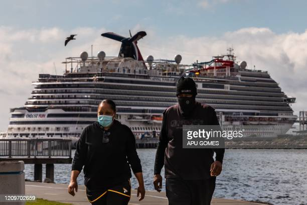 TOPSHOT A couple wearing face masks as a preventive measure against the spread of the COVID19 Coronavirus walk at the Marina Long Beach with Cruise...