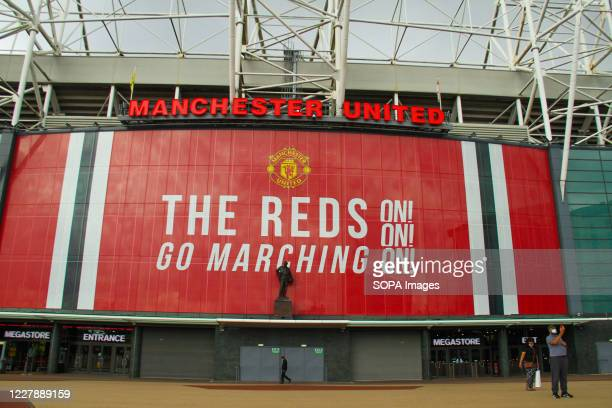 A couple wearing face masks as a preventive measure take photos outside the Old Trafford stadium in Manchester The Government has made it mandatory...