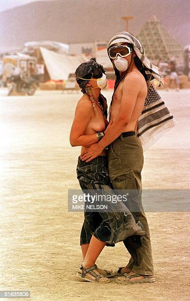 A couple wearing face masks embrace during a dust storm 05 September in the Black Rock Desert of Nevada site of the 'Burning Man' festival Some 15000...