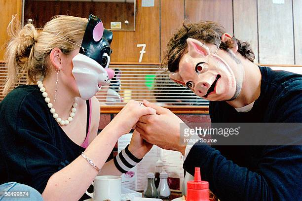 couple wearing face masks in cafe - cat face mask stock pictures, royalty-free photos & images