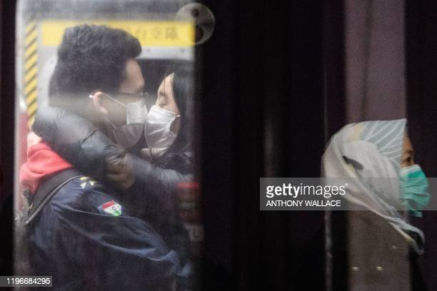 Couple wearing face masks kiss on an underground metro train as another passenger is reflected on a platform glass door during a Lunar New Year of...