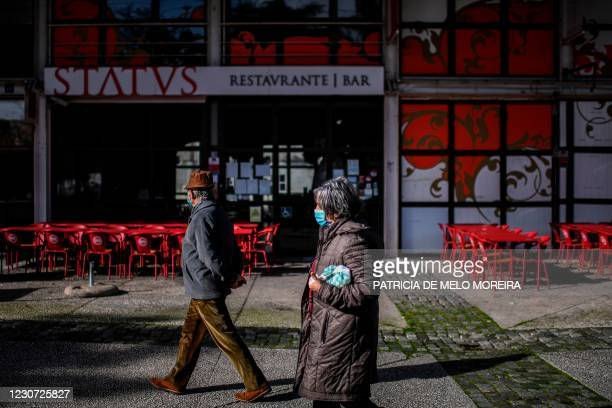 Couple wearing face masks pass by a closed restaurant at Parque das Nacoes in Lisbon on January 22, 2021. - Portugal has closed schools for two weeks...