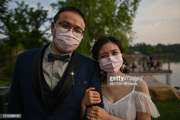 A couple wearing face masks poses for a photo after a photoshoot next to East Lake in Wuhan in China's central Hubei province on April 19 2020 The...