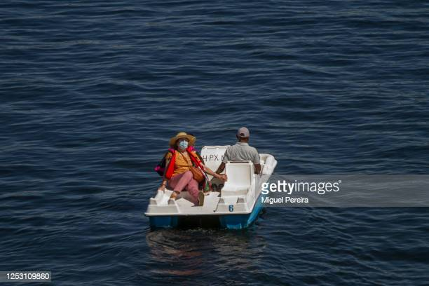 A couple wearing face masks rides on a pedal boat at San Juan swamp on June 28 2020 in San Martin de Valdeiglesias Spain The City Council of San...