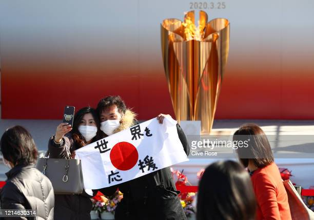 Couple wearing face masks takes selfie photographs in front of the Olympic flame with holding the national during the 'Flame of Recovery' special...