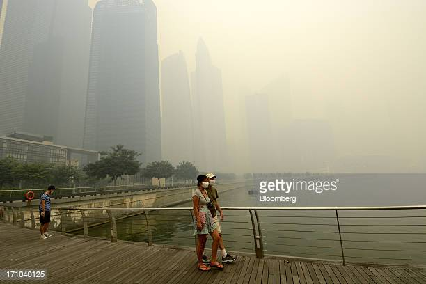Couple wearing face masks walk along the boardwalk at Marina Bay as buildings in the central business district stand shrouded in smog in Singapore,...