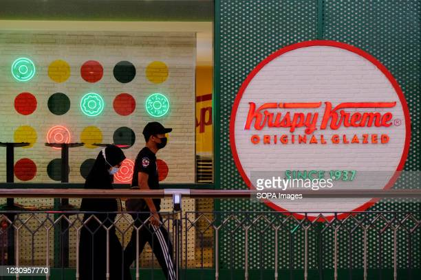 Couple wearing face masks walk past an American doughnut company the Krispy Kreme.
