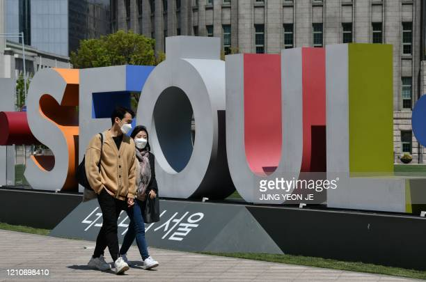 A couple wearing face masks walk through Seoul Plaza in front of the city hall in Seoul on April 23 2020 South Korea's economy saw its worst...
