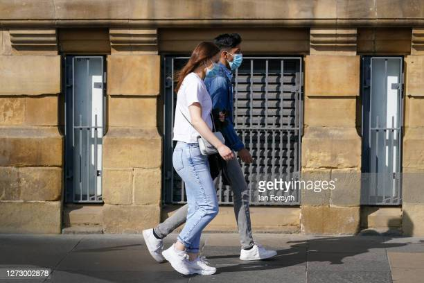 A couple wearing face masks walk through the centre of Newcastle on September 17 2020 in Newcastle upon Tyne England Almost two million people in...