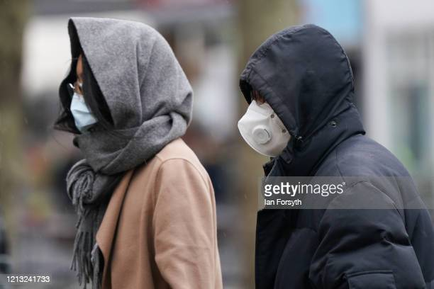 Couple wearing face masks walk through York city centre as the UK adjusts to life under the Coronavirus pandemic on March 18, 2020 in York, England....