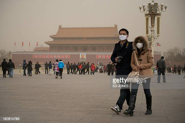 A couple wearing face masks walks on Tiananmen Square during a sand storm in heavily polluted weather in Beijing on February 28 2013 Beijing...