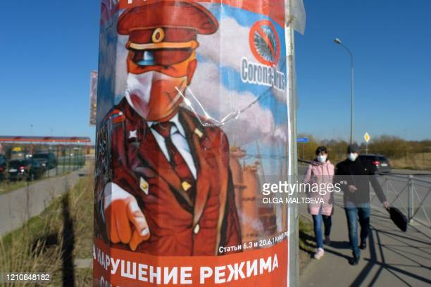 A couple wearing face masks walks towards a poster depicting a law enforcement officer warning of punishment for breaking selfisolation regime in...