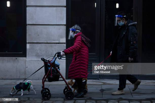 Couple wearing face visors walk dogs near Piccadilly Circus on November 19, 2020 in London, England. The United Kingdom is currently under...