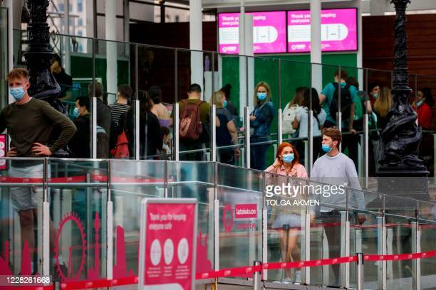 Couple wearing facemasks as a precaution against the spread of the novel coronavirus as they queue for the London Eye attraction in central London on...