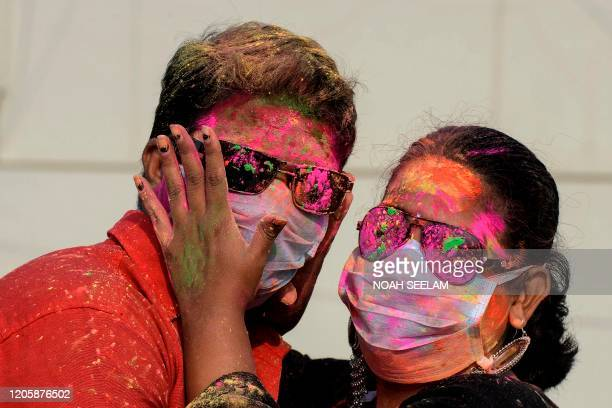 A couple wearing facemasks as a preventive measure against the COVID19 coronavirus apply smear their faces with coloured powder during a friends...