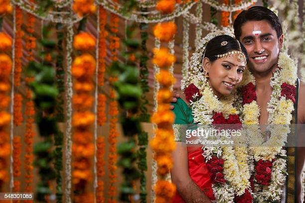 Couple wearing garlands standing together on their wedding day