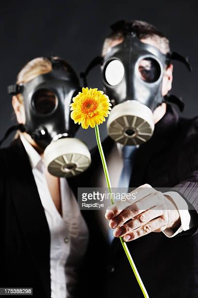Couple wearing gas masks hold flower: allergies or pollution?