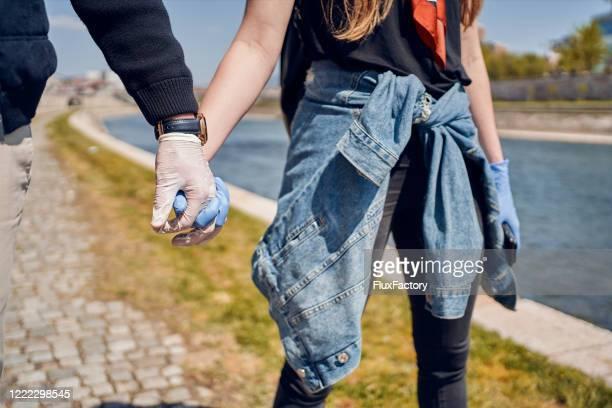 couples retenant des mains de fixation de gants pendant une pandémie de coronavirus - gant de chirurgie photos et images de collection