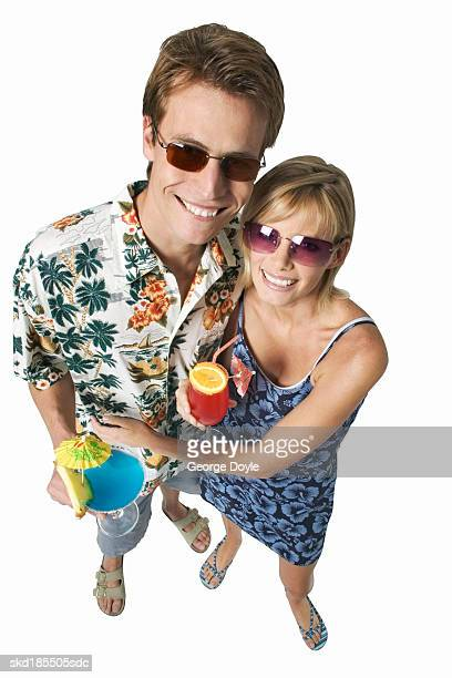 couple wearing holiday clothes and drinking cocktails - travel14 stock pictures, royalty-free photos & images