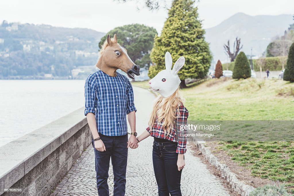 Couple wearing horse and rabbit masks holding hands, Lake Como, Italy : Stock Photo