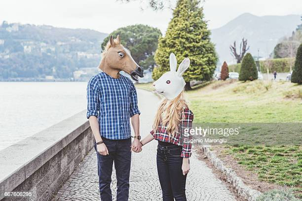 couple wearing horse and rabbit masks holding hands, lake como, italy - freaky couples stock photos and pictures